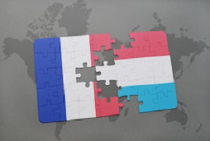 puzzle with the national flag of france and luxembourg on a world map background. 3D illustration